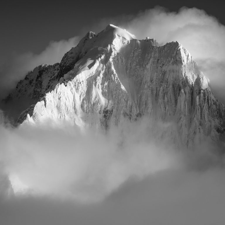 Black and white photo of the Aiguille Verte and the summits of the Alps Chamonix in clouds and fog after a snowstorm.