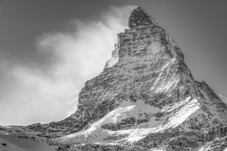 Le sommet de montagne noir et blanc du Matterhorn dans les nuages sous des rayons de soleil après une tempête sur le Mont Cervin