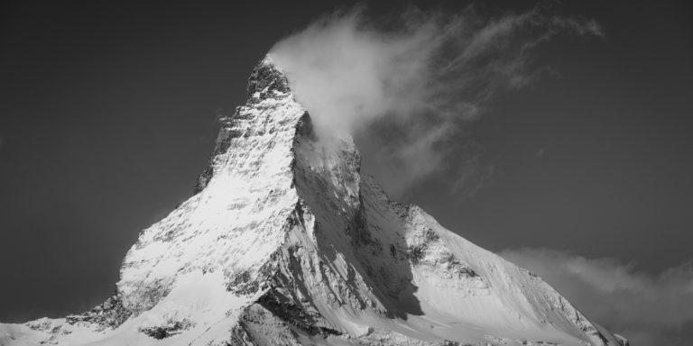 Matterhorn - Panorama d'un sommet de montagne sous la neige qui fume dans une mer de nuage