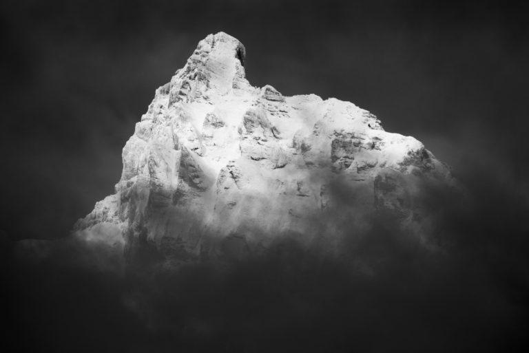 Le petit Muveran - sommet de montagne d'Ovronnaz noir et blanc dans une mer de brume et de nuages
