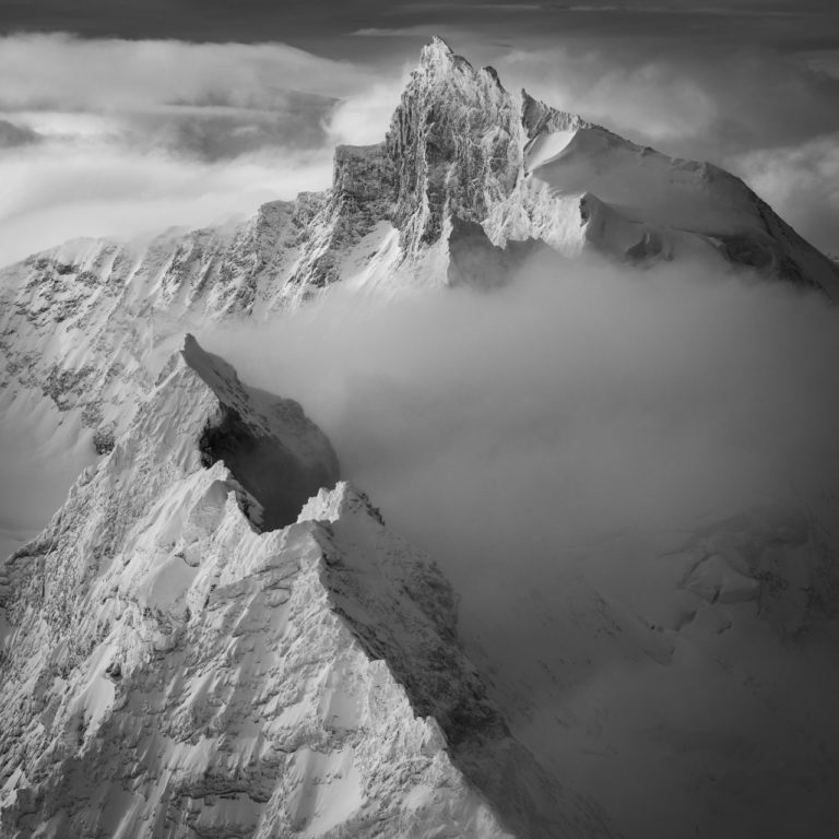 black and white alpine mountain picture in a sea of clouds